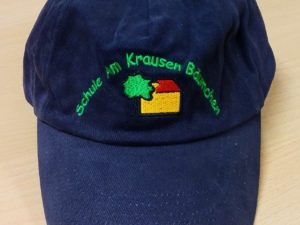 Blaue Cappy mit buntem Schullogo der Schule am Krausen Bäumchen.